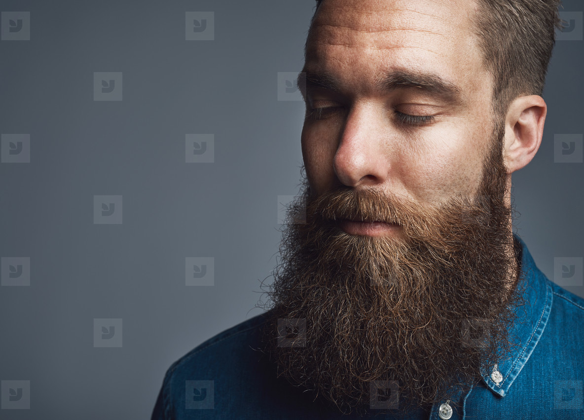 Bearded man in blue denim with eyes closed