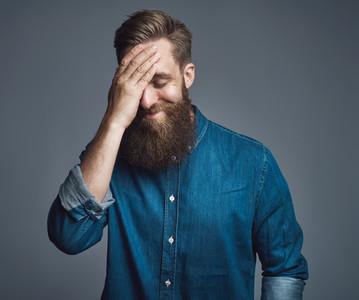 Bearded man in blue denim shirt with hand on head