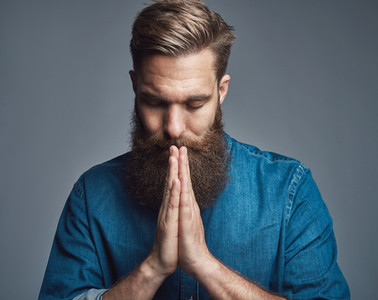 Prayerful bearded young man with palms together