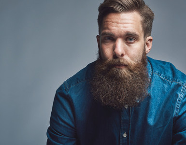 Close up on serious man in blue shirt and beard