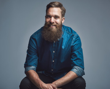 Handsome smiling man in blue shirt and beard