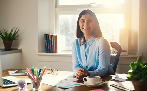 Confident business woman sitting at desk