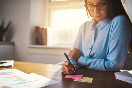 Business woman writing notes on post it