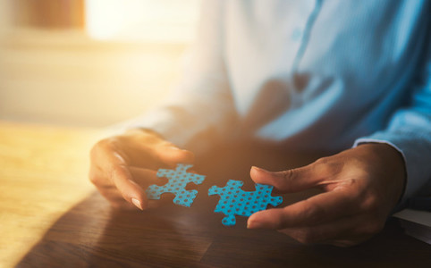 Business woman connecting puzzles