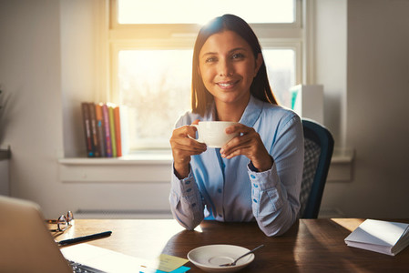 Woman working at office drinking coffee