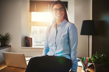 Confident woman sitting on desk