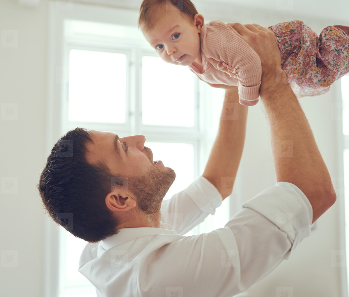 Young father holding his baby girl up in the air