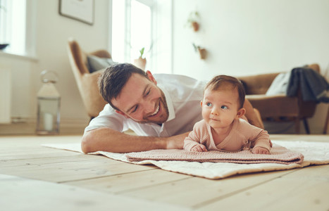 Smiling father lying with his infant daughter at home