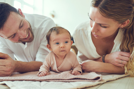 Smiling young parents lying with their baby girl at home