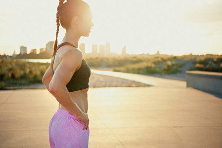 Toned fit young woman backlit by the sunrise