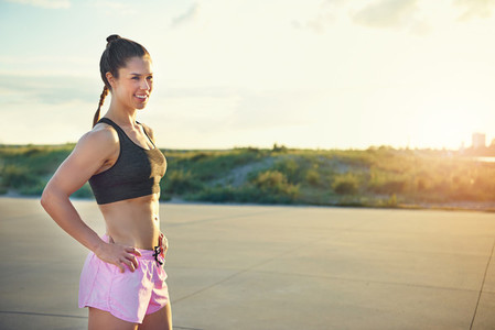 Fit young female athlete standing outside