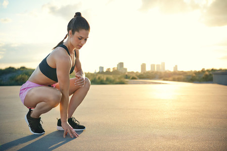 Woman ready to run while squatting near ground