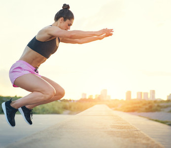 Young woman doing crossfit exercises outdoors