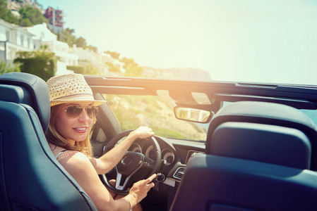 Young woman in convertible car looking back