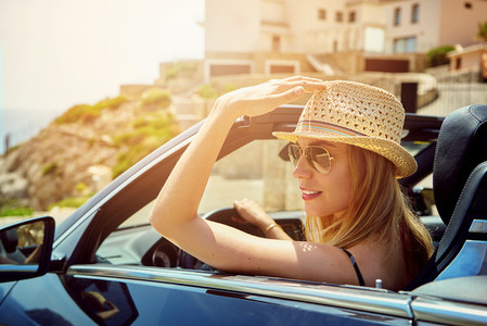 Grinning young woman driving convertible car