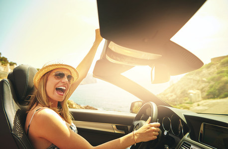 Shouting or celebrating woman driving her car