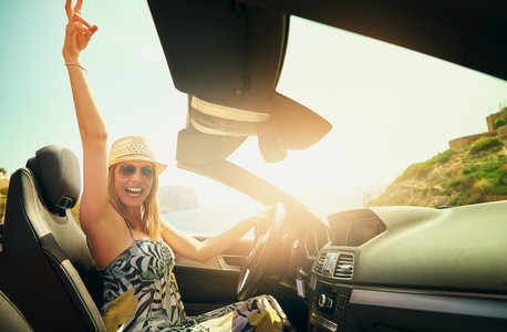Excited woman gesturing with hand while driving