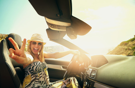 Woman driving cabriolet and showing two fingers