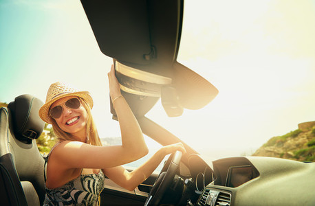 Happy young female driving cabriolet in mountains