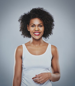 Portrait of smiling happy woman  black woman on grey background