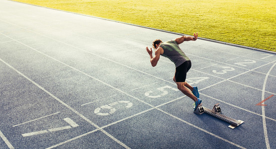 Sprinter taking off from starting block on running track