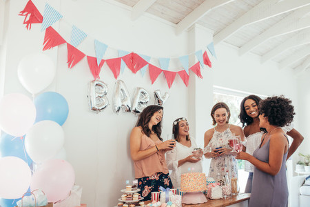 Pregnant woman celebrating baby shower with friends