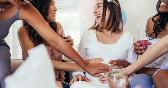 Smiling friends touching tummy of pregnant woman