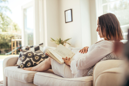 Pregnant woman relaxing on sofa reading  book