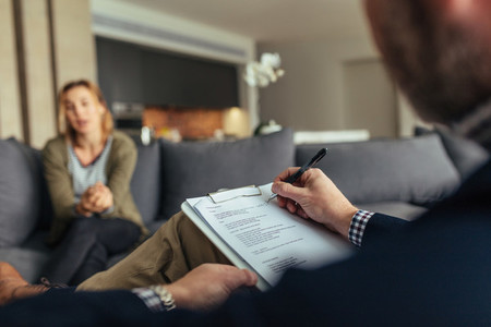Psychologist writing notes during a therapy session with patient