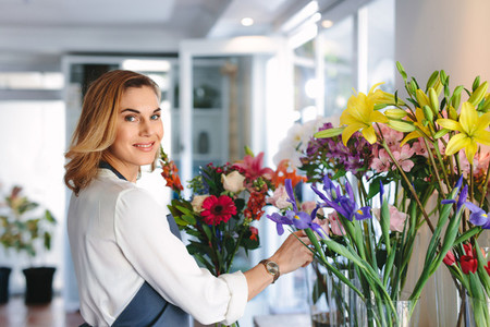 Female florist creating bouquet of flowers