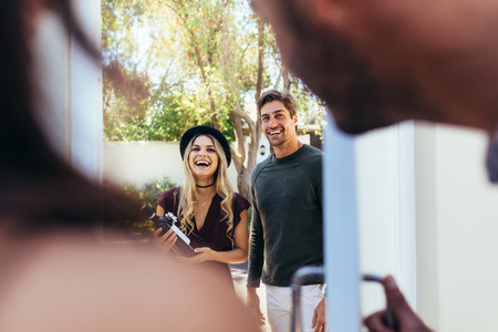 Smiling young couple at entrance door with wine bottle
