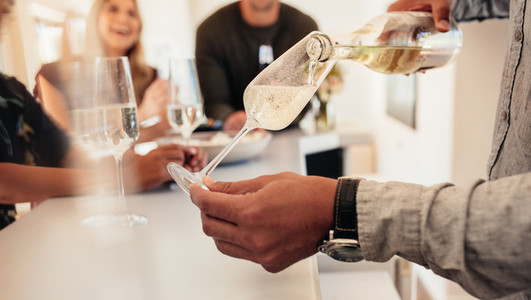Man serving drinks to friends at new house