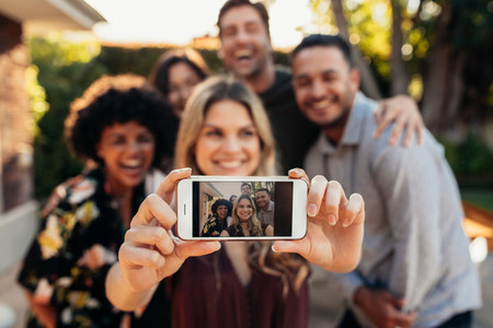 Joyful friends taking selfie during outdoor party