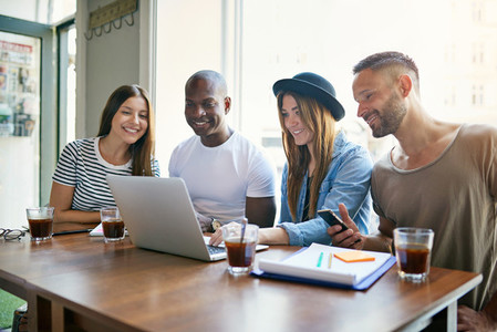 Young people at desktop smiling and working