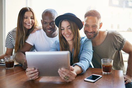 Woman sharing something on tablet with friends