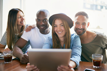 Group of smiling people sitting with tablet
