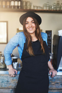 Happy barista leaning against counter in cafe