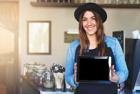 Coffee house worker holding blank tablet computer