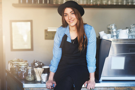 Smiling female barista sits on cafe counter