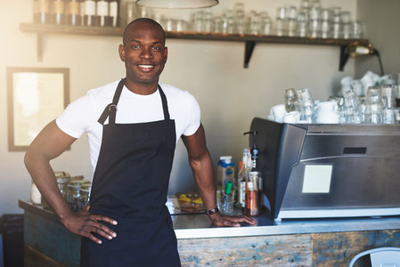 Confident male coffee house owner at counter