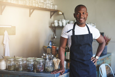 Handsome black entrepreneur stands by cafe counter