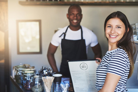 Cheerful customer with menu and cafeteria owner