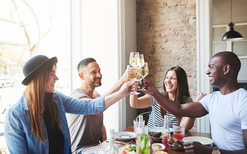 Group of young adults drinking together at table