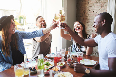 Group of four laughing adults toasting drinks