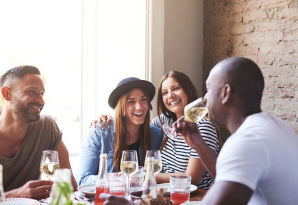 Two ladies laughing while male friends drink wine