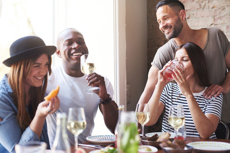 Group of adults celebrating with wine at lunch