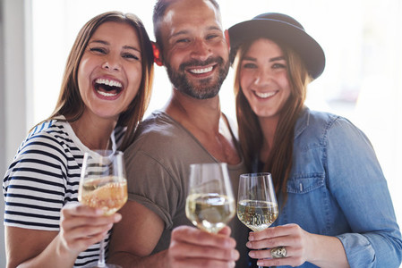 Three laughing friends with wine glasses