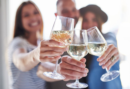 Toasting wine glasses with people behind them