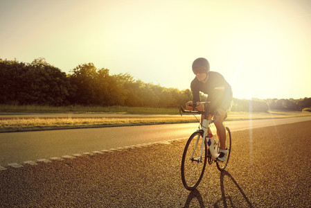 Bicyclist on road bike at sunrise