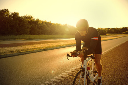 Light flares from sun over man training on bike